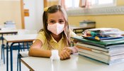 girl_sitting_at_her_chair_and_table_in_the_classroom_wearing_a_mask_to_protect_herself_during_the...