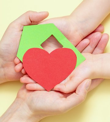 hands_holds_green_paper_house_with_red_heart