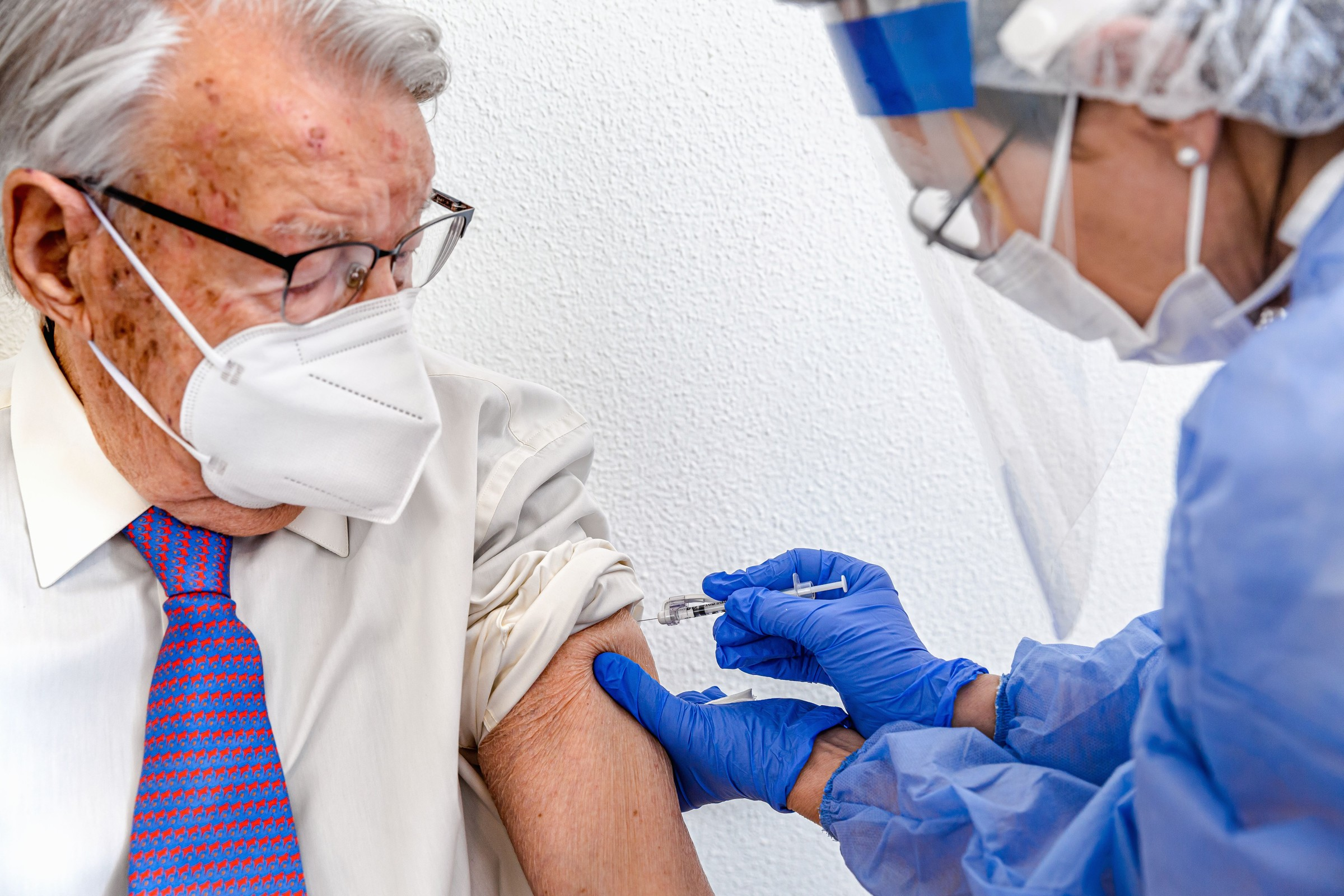 elderly_man_in_mask_watches_as_nurse_in_protective_suit_and_covid_mask_gives_him_coronavirus_vaccine